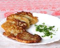 Pancake di patata su un piatto bianco con il sauc dell'aglio e della panna acida Fotografie Stock Libere da Diritti