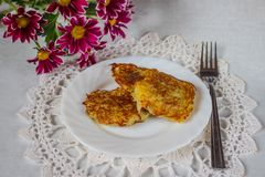 Pancake di patata tostati su un piatto con i fiori e un tovagliolo fotografia stock libera da diritti