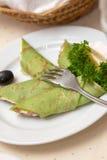 Pancake on dish. Green pancake on white dish with fork Stock Image