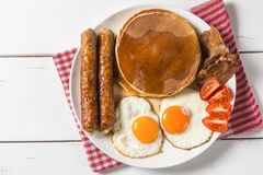 Pancake with egg, sausage, bacon and maple syrup. The view from the top. Copy-space stock photos