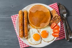 Pancake with egg, sausage, bacon and maple syrup. The view from the top. Copy-space stock image