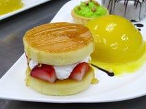 Pancake en Moussecake op witte plaat Verfraai met aardbei Elk ding is heerlijk Royalty-vrije Stock Fotografie