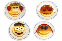 Pancake Faces. Four pancakes decorated with funny faces Stock Photo