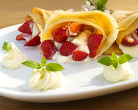 Pancake filled with strawsberries and garnished with mint, syrop and whipped cream Royalty Free Stock Photo
