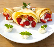 Pancake filled with strawsberries and garnished with mint, syrop and whipped cream Royalty Free Stock Image