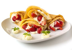 Pancake filled with strawsberries and garnished with mint, syrop and whipped cream Stock Photos