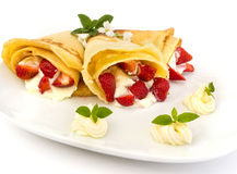 Pancake filled with strawsberries and garnished with mint, syrop and whipped cream Royalty Free Stock Photography