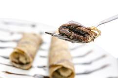 Pancake on a fork. Pancake with liquid chocolate on a fork. With blurred pancakes on a plate in background Royalty Free Stock Image