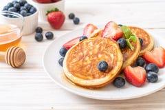 Pancake with fresh blueberries, fresh strawberries and honey. Souffle pancake with fresh blueberries, fresh strawberries and honey stock photos
