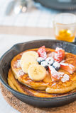Pancake with fresh strawberry blueberry and banana. On pan royalty free stock photography