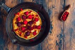 Pancake fritti casalinghi su una padella nera del ghisa Sopra sono le bacche, i lamponi, i mirtilli rossi e le more fotografia stock