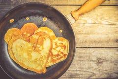 Pancake fritti - cuore su una padella del ghisa Vista superiore Immagini Stock Libere da Diritti