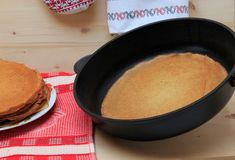 Pancake on a frying pan and pile of pancakes on a dish. Pancake on a frying pan and pile of pancakes on a dish and on wooden  table Stock Image
