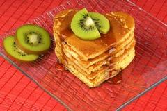 Pancake Heart-shaped con la frutta di kiwi e dello sciroppo Fotografia Stock