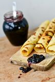 Pancake. Homemade pancake crepe     with    blueberry jam and ices sugar on black slate Stock Images