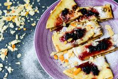 Pancake. Homemade pancake crepe     with    blueberry jam and ices sugar on black slate Royalty Free Stock Photography