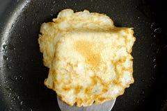 Pancake on the hot black pan Stock Photography