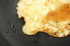 Pancake on the hot black pan Royalty Free Stock Images