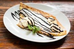 Pancake with a ice-cream, banana and cholate. Sweet pancake with a banana and cholate on white plate Royalty Free Stock Photos
