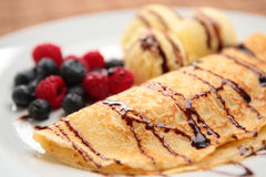 Pancake with Ice Cream and Fruits. A delicious pancake with fresh fruits (raspberries and blueberries), vanilla ice cream and chocolate sauce, served in a white Stock Photos