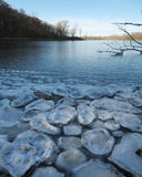 Pancake Ice on a Frozen Lake. Pancake ice lines the shore of a frozen lake Stock Photos