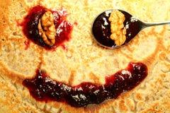 Pancake with jam and walnuts. Homemade pancake smiling face with jam and walnuts Stock Photo