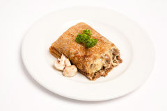 Pancake with mashrooms and meat. On white plate stock photo