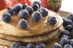 Pancake Meal. Pancakes with fresh blueberries and syrup on a plate. Strawberries in the background stock images