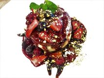 A pancake with Nutella, which adds more aromas with mixed berry compote and pistachio crumbs royalty free stock photo