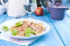 Pancake olandesi con il prosciutto per i colori luminosi della prima colazione, fondo blu Saporito e calorico Vetro di acqua Spaz immagini stock libere da diritti