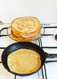 Pancake in pan and stack of prepared pancakes Royalty Free Stock Photos
