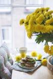 Pancake per la vista della prima colazione dalla finestra Vaso con i fiori gialli immagine stock libera da diritti
