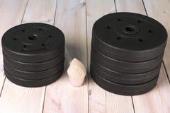 Pancake per le teste di legno sul pavimento e sulla proteina di legno Attrezzatura di sport fotografia stock