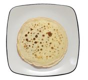 Pancake on plate. Round spread pancake in center of square plate isolated on white background Royalty Free Stock Images