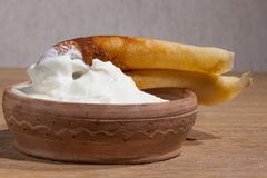 Pancake on a plate with sour cream closeup. Close-up of a pancake with sour cream in and a clay dish on an oak table Royalty Free Stock Photos