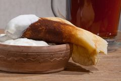 Pancake on a plate with sour cream closeup. Close-up of a pancake with sour cream in and a clay dish on an oak table Royalty Free Stock Image