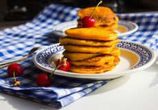 Pancake with pumpkin and cherry. Blue tablecloth. Tablecloth in a cage Stock Photo