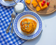 Pancake with pumpkin and cherry. Blue tablecloth. Tablecloth in a cage Royalty Free Stock Photo