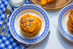 Pancake with pumpkin and cherry. Blue tablecloth. Tablecloth in a cage Royalty Free Stock Photos