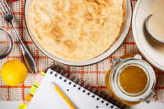 Pancake. With recipe book on kitchen table Royalty Free Stock Image