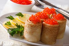 Pancake rolls filled with red caviar, horizontal Royalty Free Stock Photo