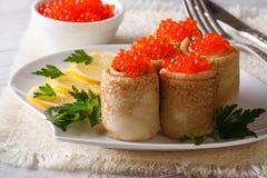 Pancake rolls with red caviar and lemon. Horizontal Stock Photo