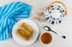 Pancake rolls with stuffed, tea, sugar cubes, teapot, teaspoon,. Pancake rolls with stuffed in plate, cup of tea, sugar cubes, teapot, teaspoon, napkin on wooden Royalty Free Stock Photography