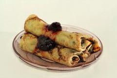 Pancake rotolati con l'ostruzione di fragola su una lastra di vetro Fotografia Stock