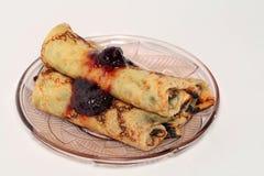 Pancake rotolati con l'ostruzione di fragola su una lastra di vetro Immagine Stock Libera da Diritti