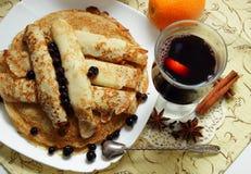 Pancake, rotolati nei tubi ed in un vetro di vin brulé caldo Fotografie Stock