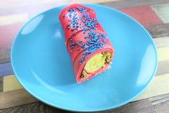 Pancake rotolato interessante riempito di briciole della crema e della banana e dei biscotti del cioccolato sulla banda nera con  fotografia stock