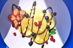 Pancake rubicondo con le bacche nei raggi luminosi del sole di mattina Immagine Stock