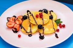 Pancake rubicondo con le bacche nei raggi luminosi del sole di mattina Fotografie Stock