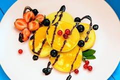 Pancake rubicondo con le bacche nei raggi luminosi del sole di mattina Immagini Stock